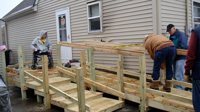 People building a wheelchair ramp.